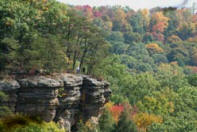 edge of cliff over looking tall forrest. trres are red and orange colors of fall.