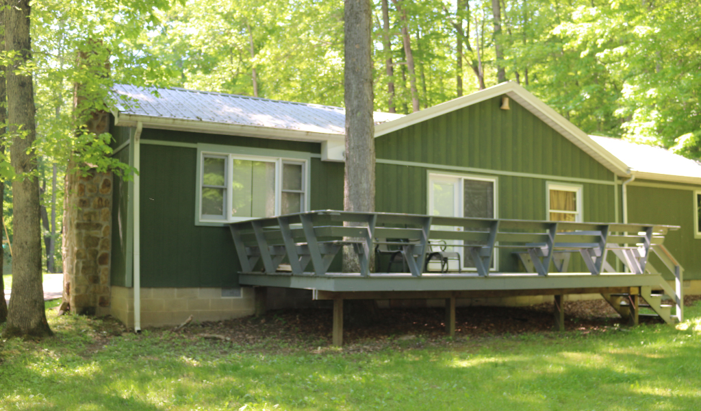 sunny day with tall trees around property. Green siding with long front deck overlooking the woods.