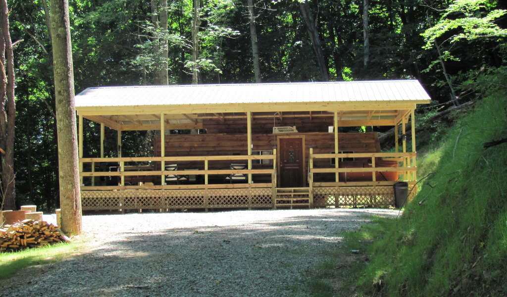 sunny day view of cabin with wde porch and metal roof. large wooded area around cabin,